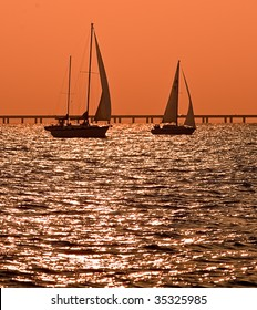 Silhouette of two sailboats against the orange dusk sky.