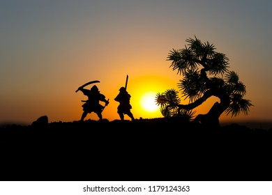 Silhouette of two samurais in duel near tree. Picture with two samurais and sunset sky. Selective focus