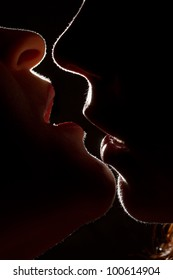 Silhouette of two sexy woman kissing in darkness through light