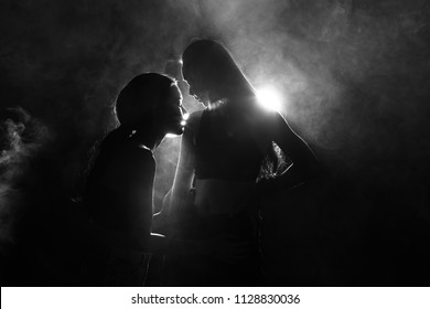 Silhouette of two sexy woman kissing holding in darkness through light and smoke, they have good feeling on first date flirt and want to love best friends forever, girls in long straight black hair