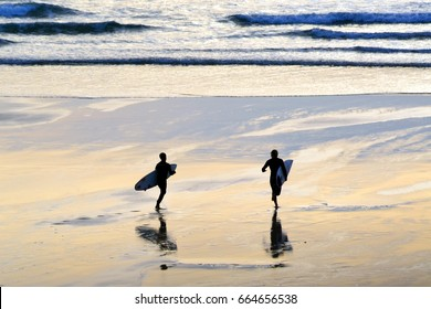 silhouette of two surfers going for a sunset surf