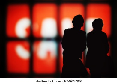 Silhouette of two woman shopper against a Sale sign in a shop window.
