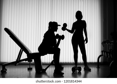 Silhouette of two women lifting weights in gym.