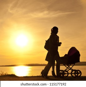 Silhouette of two women walking with a perambulator.