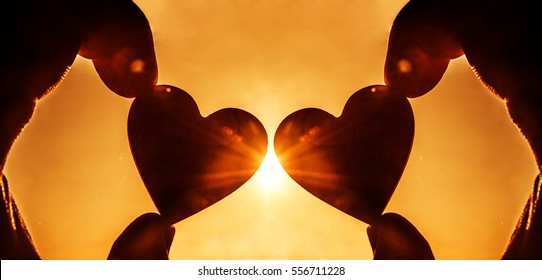 silhouette of two wooden Heart Shape in the Hand on the Sky Background. sun rays. Sunset or sunrise. yellow sky. empty copy space for inscription. happy new Valentine's day idea, sign, symbol, concept