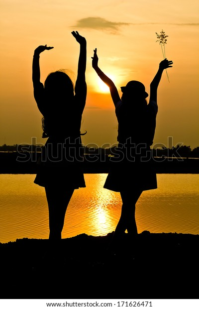 The silhouette of two young girls over beautiful twilight sunset.