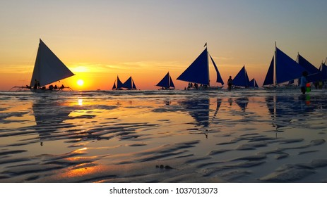 Silhouette of typical sailing boats at sunset in Boracay island - Exclusive travel destination in Philippines.