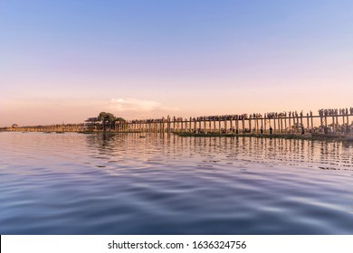 Silhouette of U Bein Bridge is a crossing that spans Taungthaman Lake, Amarapura in Myanmar. oldest & longest teakwood bridge in world. Tourists on bridges and boat grooves to watch sunset. Oct 2019