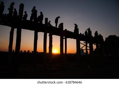 Silhouette U Bein bridge with many people at Taung Taman lake, Amarapura, Myanmar