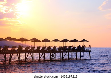 Silhouette of umbrellas and deck chairs on sunset sky background, Aegean Sea, Turkey
