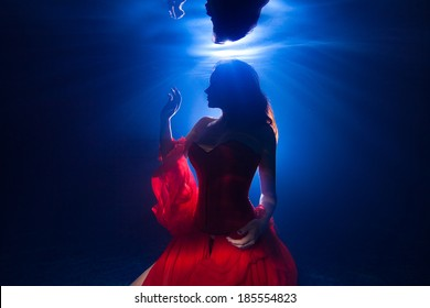silhouette underwater photo pretty young girl  with dark long hair wearing red dress