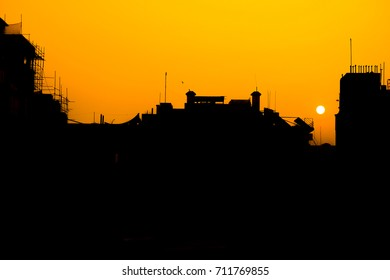Silhouette of unidentified building during sunrise in glowing orange color