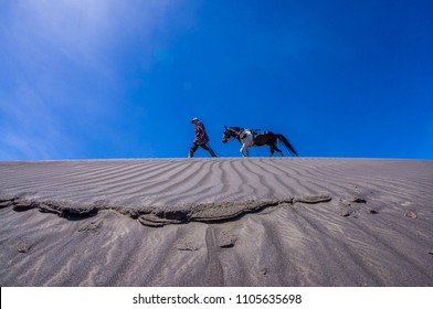 Silhouette of unidentified local people or Bromo Horseman at the mountainside of Mount Bromo, Semeru, Tengger National Park, East Java of Indonesia.