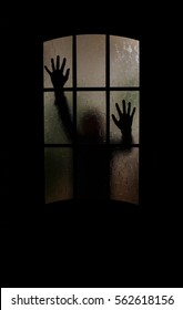 Silhouette of an unknown man with his hands on a door through a closed glass door