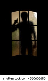 Silhouette of an unknown man shows the index finger through a closed glass door
