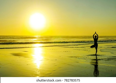 silhouette of unknown unrecognizable woman standing on beach sea water practicing yoga and meditation looking to the sun on the horizon with an amazing beautiful orange sunset sky