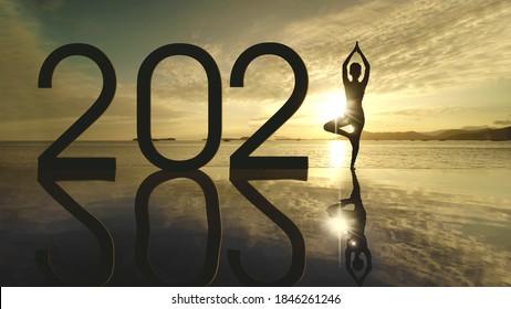 Silhouette unbekannter Frau, die Yoga am tropischen Strand ausübt, während sie bei Sonnenuntergang mit der Nummer 2021 steht