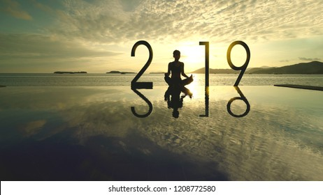Silhouette of unknown woman meditating with number 2019 on the beach at sunset time