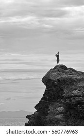 Silhouette of unrecognizable Fijian man stands on a sea cliff in the Yasawa Islands of Fiji. Travel Fiji concept,  copy space (BW)