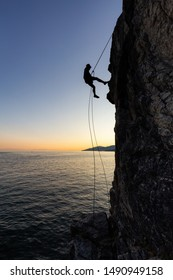 Silhouette of a Unrecognizable man rappelling down a steep cliff on the rocly ocean coast during a sunny summer sunset. Taken in Lighthouse Park, West Vancouver, British Columbia, Canada.