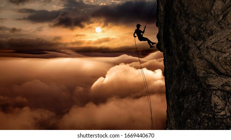 Silhouette of a Unrecognizable man rappelling down a steep cliff on top of a mountain during a sunny and cloudy vibrant sunset or sunrise. Concept: Sport, , Adventure, Explore, Lifestyle, Freedom