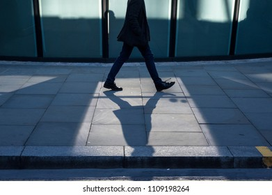 Silhouette of an unrecognizable man walking in a generic city. Shadows and reflections. Concept management, corporate strategies, future cities, employment, digital transformation, business, finance