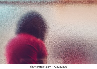Silhouette of unrecognizable sad autistic girl behind stained glass window sitting alone in the backyard