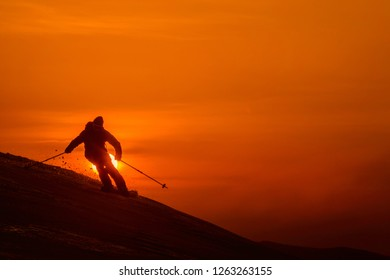 SILHOUETTE Unrecognizable skier shredding the fresh untouched snow on the steep hill at sunset. Breathtaking shot of extreme pro skier speeding down the snowy mountain on a beautiful evening in Niseko