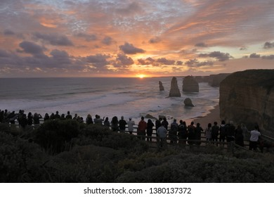 Silhouette of unrecognizable tourists at Port Campbell National Park, looking at the Twelve Apostles during sunset along the Great Ocean Road in Victoria, Australia.