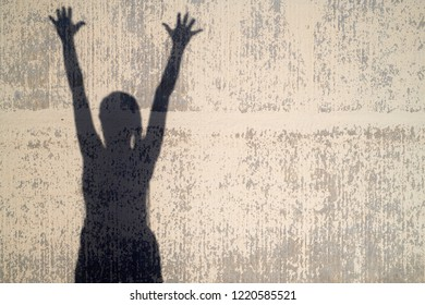 Silhouette of unrecognizable woman holding her arms up in the air showing happiness. Decayed background in sunlight.