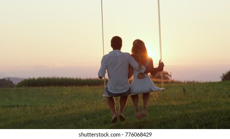 SILHOUETTE: Unrecognizable young couple swaying on swing under green tree observing the romantic golden spring sunset. Man and woman in love enjoying peaceful view of summer day turning into night.