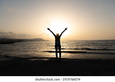 Silhouette of unrecognized young woman with protective surgical face mask performs yoga stretching exercises at the beach at dusk during coronavirus pandemic.