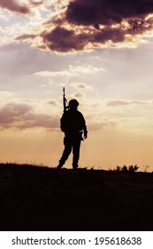 Silhouette of US soldier with rifle  against the sunset