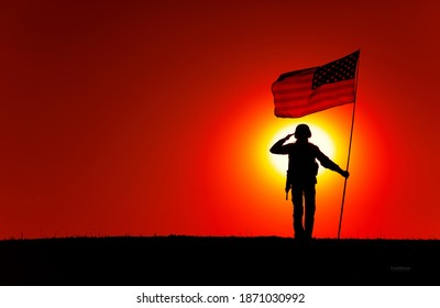 Silhouette of USA armed forces soldier, army infantryman or Marine Corps fighter veteran saluting while standing with national flag on sunset background. Military victory and glory, fallen remembrance