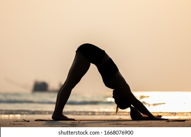 Silhouette Vacation of Asian woman relaxing in yoga Downward Facing dog or Adho Mukha Svanasana pose on sand and beach with sunset sea in Thailand Tropical island,Feel comfortable and relax in holiday