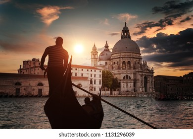 Silhouette of Venezian gondolier punting gondola in Grand canal.