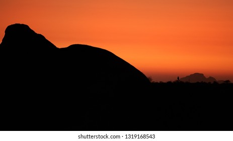 Silhouette of Verreaux's or Giant Eagle-owl, Bubo lacteus perched on famous rounded granite rock of Spitzkoppe area against orange sky. Late evening in rocky desert landscape, Spitzkoppe, Namibia.