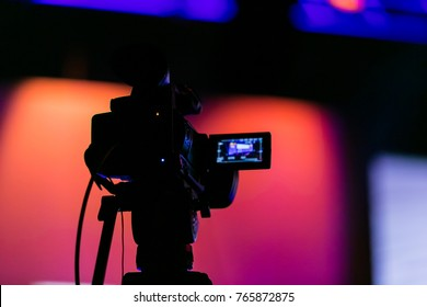 Silhouette of a video camera capturing an event on stage. Live streaming tv. Breaking news. News event. Story. Reporter. Live Broadcast