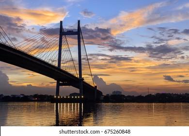 Silhouette of Vidyasagar Setu bridge at twilight .