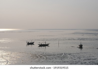 The silhouette view of 3 sailboats on the beach meets the shining morning sun