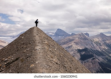 A silhouette view of an anonymous hiker stands on top of a small hill shaped like a pyramid in front of the Canadian Rockies in Yoho National Park.