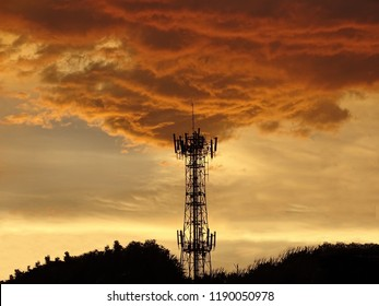 Silhouette view of cellphone antenna under twilight sky. Silhouette the mobile communication antennas in evening sky. Antenna tower under cloud blaze. The cloud looks like a fire coming from a tower.