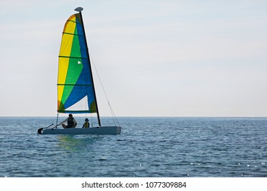 silhouette view of family of two, father and son, and catamaran boat sailing in open sea, adventure vacation concept, copy space on right