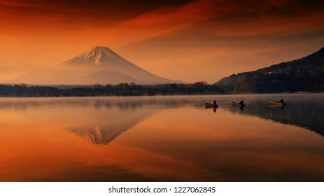 Silhouette view of fishermen on boats with mist and twilight sky during dawn at Shoji lake in Yamanashi, Japan. Landscape with beautiful skyline reflection on water with mount Fuji or Fujisan.