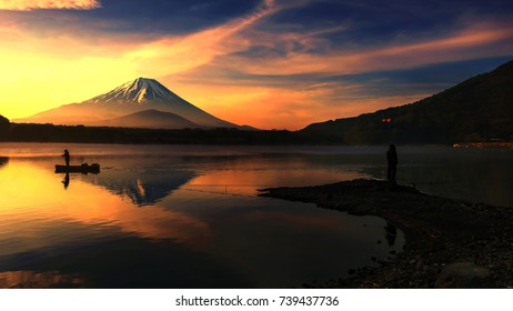 Silhouette view of fishing against sailing boat at Shoji lake with mt. Fuji view reflection during sunrise in early morning in Yamanashi, Japan.