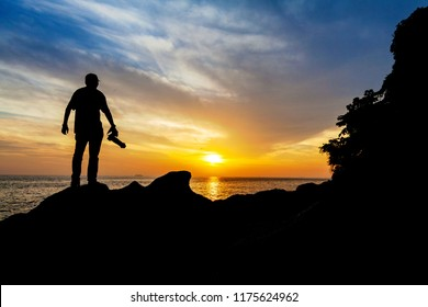 Silhouette view of male model photographer by sunrise or sunset background