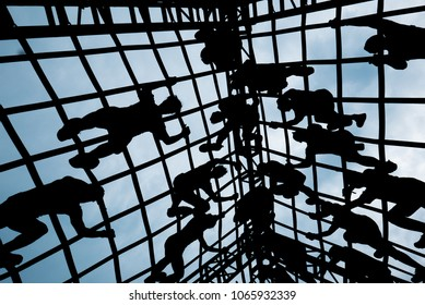 Silhouette view of people climbing on an outdoor ropes course with blue sky background in adventure park. Climbing metal grid to rooftop in playground. active  in extreme sport. Abstract