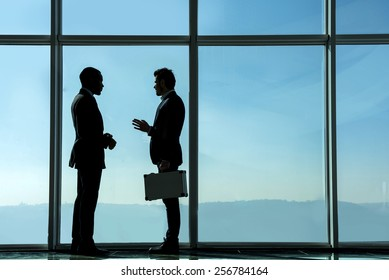 Silhouette view of two young businessmen are standing in modern office with panoramic windows.