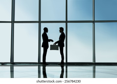 Silhouette view of two young businessmen are standing with suitcase in modern office with panoramic windows.