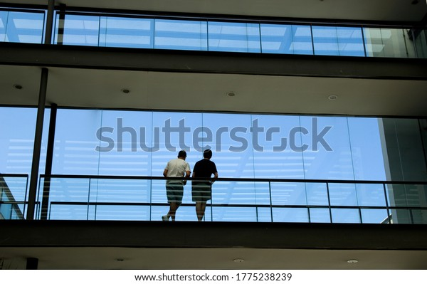 Silhouette view of two young men in a modern office building interior with panoramic windows.